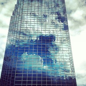 Photo of building with cloud reflections.