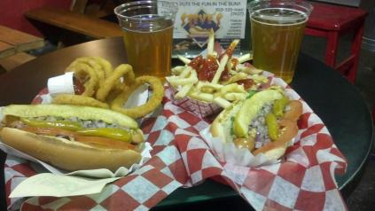 Photo of veggie hot dogs, fries, onion rings and beer.